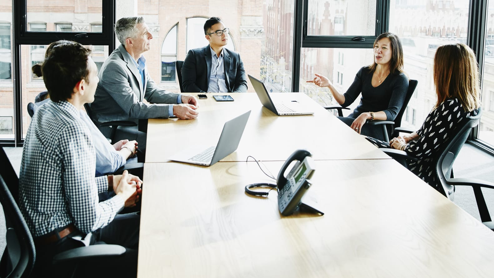 Men and Women discussing topics while sitting at a table in a conference room
