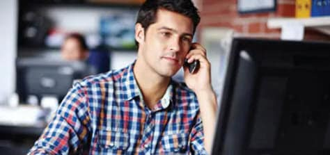 Image of man talking on the phone and looking at computer