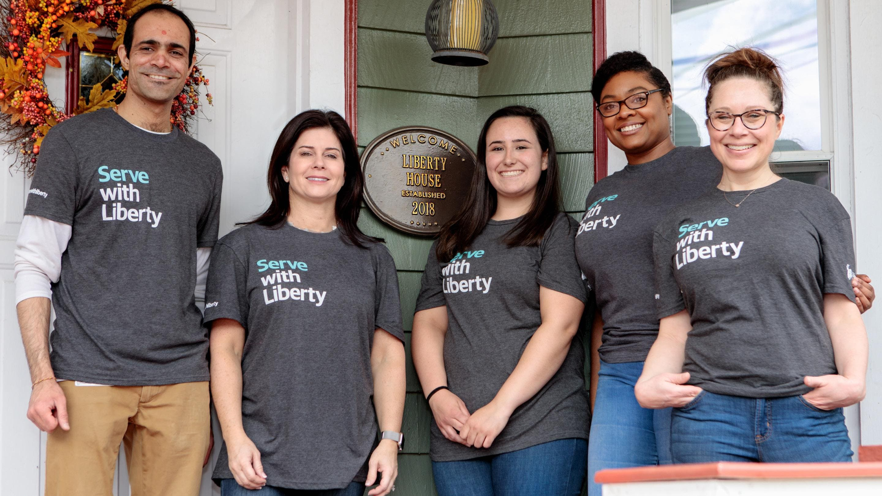 (slide 2 of 6) Liberty  Mutual Employees posing in Serve with Liberty shirts.